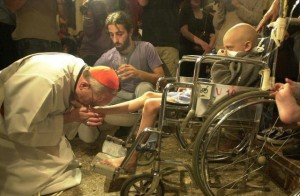 Pope Francis, when cardinal, kissing the feet of a child with AIDS after he had washed his feet.